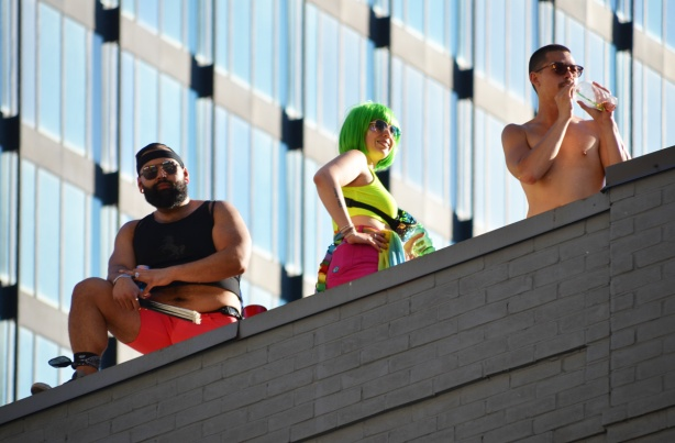 3 people on roof watching pride parade