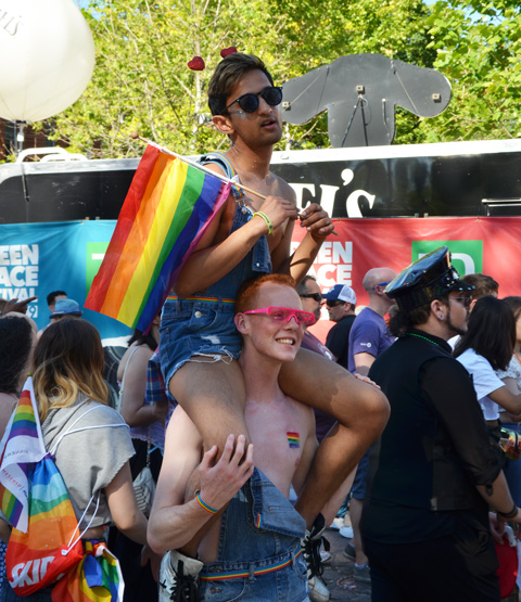 one man sitting on another man's shoulders, rainbow flag