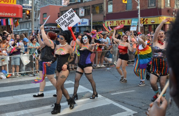 Rocky Horror theme group at pride parade with sign that says let's do the time warp again