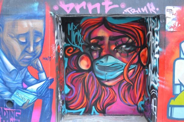 mural of woman in bright colours, reds and pinks, wearing a blue mask, tribute to health care workers.