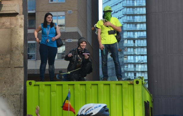 3 people on top of green container watching pride parade