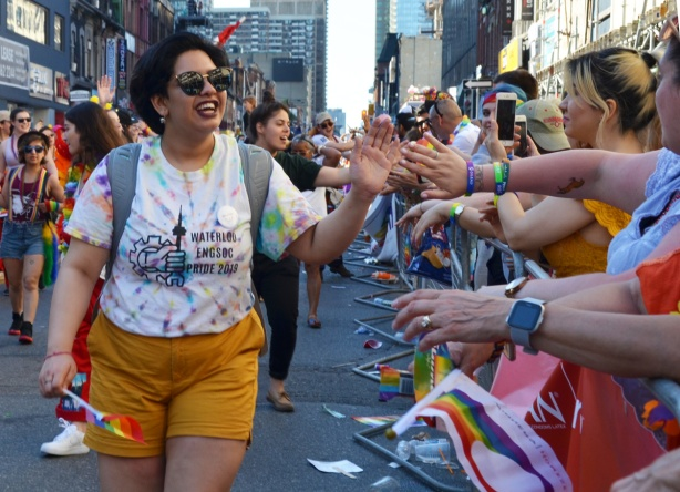 woman in Waterloo Engineering society t-shirt high fives with crowd watching pride parade