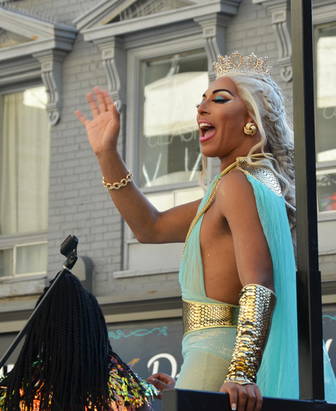 on float at pride, in long turquoise dress and platinum blond hair
