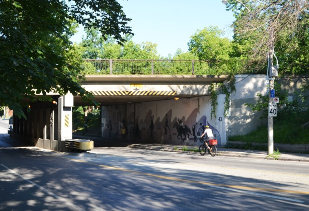 a cyclist on Dundas street about to go under the railway track bridge
