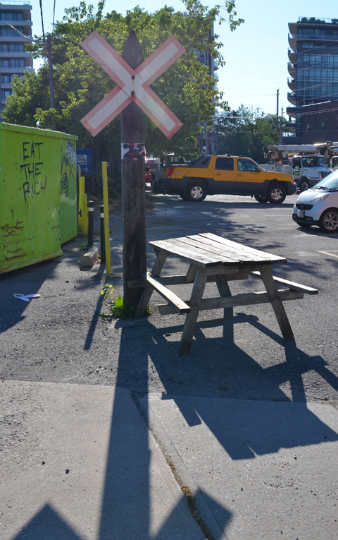 a wood picnic table at the edge of a small parking lot and beside an old railway crossing sign