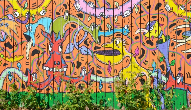 part of an Al Runt mural on a fence, orange background with lots of his typical characters in bright colours