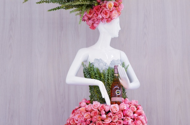 mannequin in green and pink dress and pink hat, pinks are made of roses and she is holding a bottle of rose wine from the LCBO