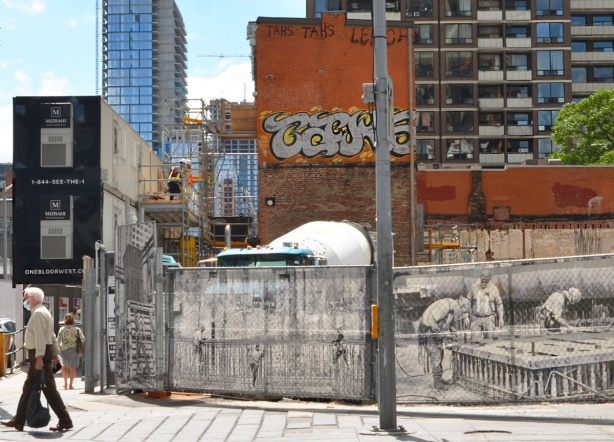 a man wearing a covid face mask walks past a construction site at Yonge and Bloor, black and white construction photos on the hoardings, old brick building in the background as well as a newer apartment building