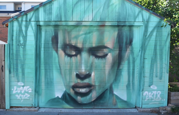 in blue tones, on a garage door, a portrait by luvsomone of a face with closed eyes