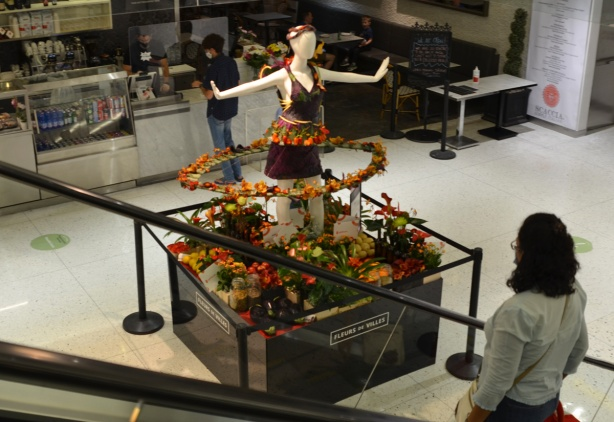 a mannequin decorated with flowers stands at the bottom of an escalator at the Manu Life center, as part of Fleurs de Villes project