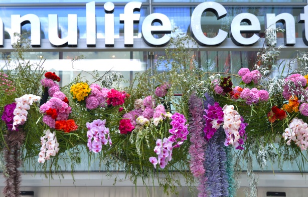 one of the glass entrances to the ManuLife center on Bloor street, decorated with flowers