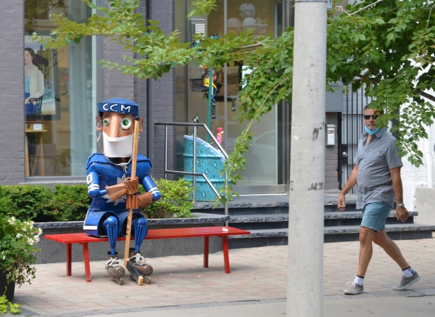 a metal statue of a hockey player in Toronto Maple Leaf blue sits on a bench outside a gallery, wearing a covid face mask, as a man walks past