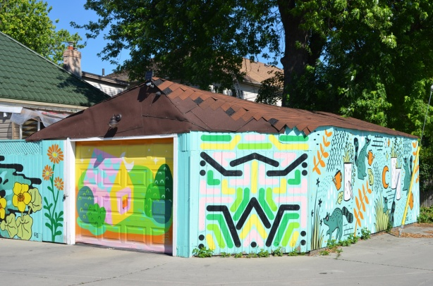 at the intersection of a street and an alley, a garage with street art on all sides facing road, with four different murals on it