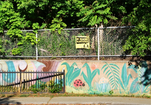 a sign that says slow down on a fence above a concrete wall with paintings of plants and flowers on it