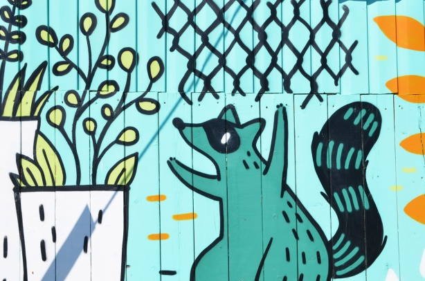teal raccoon in a mural looking at a plant growing in a white planter
