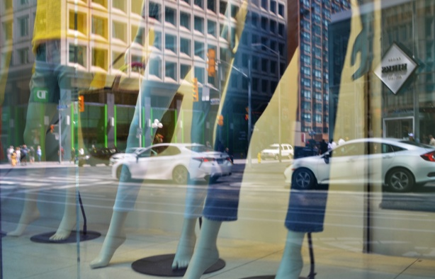 reflections in a store window, legs of mannequins in cut off jeans, white cars traffic on the street