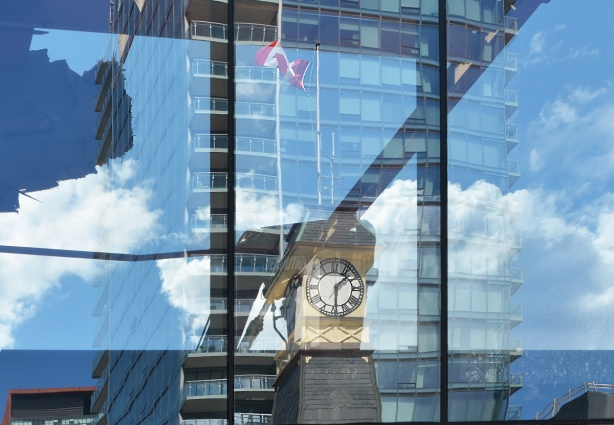 reflections of Yorkville clock tower in the glass condo across the street
