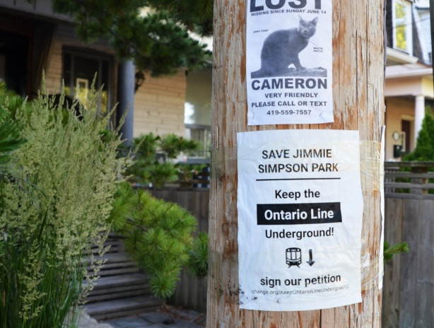 posters on a wood utility pole, bottom is to protest Ontario Line (subway) and to keep it underground and not run it through Jimmie Simpson parl. upper poster is for a lost cat