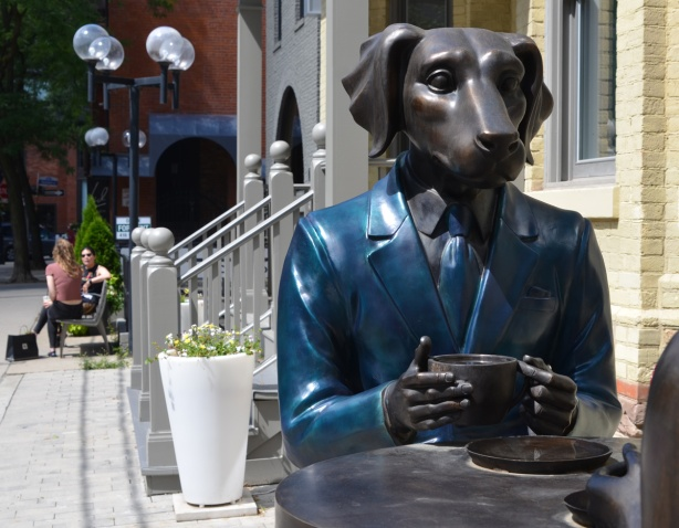 sculpture on Scollard street, a dog in blue, sits at a table with a cup of coffee in his hands
