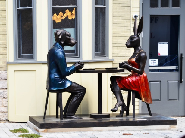 male dog in blue and female rabbit in red sitting face to face at a table with coffee, sculpture on Scollard street