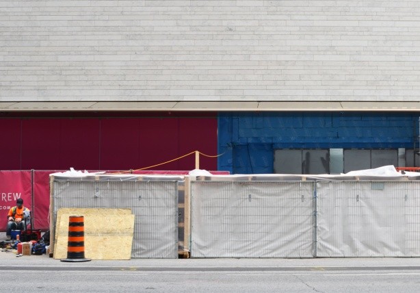 a workman sits outside beside hoardings on Bloor street in front of Holt Renfrew