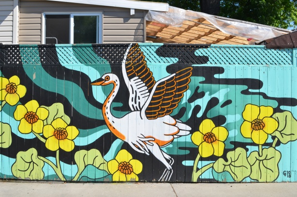 mural of a large white bird, swan?, heron?, stork?, with wings in position as if about to fly, large yellow flowers