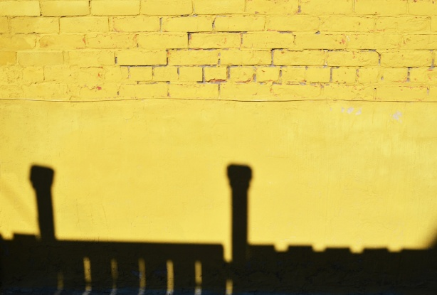 yellow wall with a black shadow of a fence along the bottom