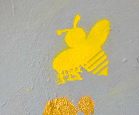 stencil graffiti of a yellow bee