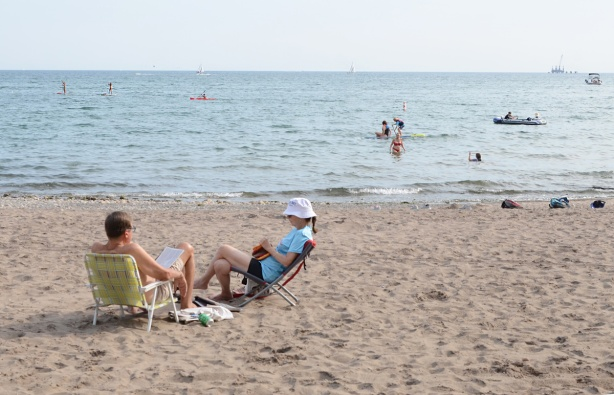 a couple sit on low chairs in the sand at Woodbine Beach, others are in the water swimming or on paddle boards
