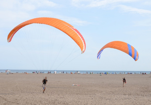two men with large kites are trying to get themselves up in the air, a woman in a bathing suit lies on the sand between them.