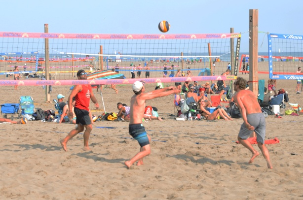 young people playing volleyball on the beach in the sane