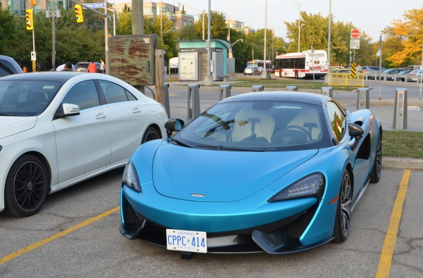 new blue Mclaren sports car parked ina parking lot at Woodbine beach, beside a white car and in front of a TTC bus stop