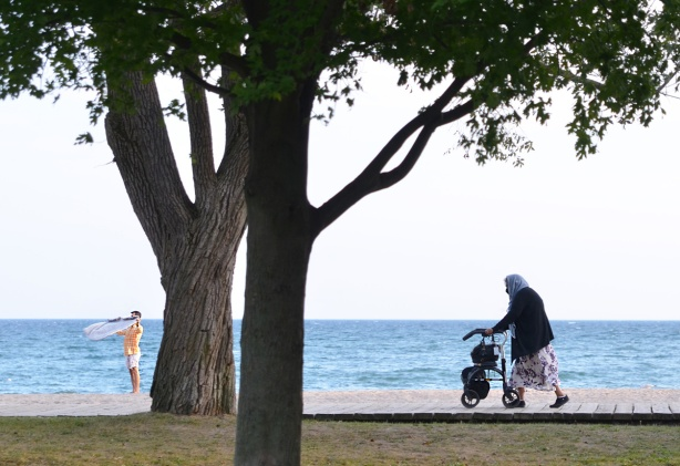 an old woman in a long purple and white skirt and a scarf over her head walks along the boardwalk with her walker