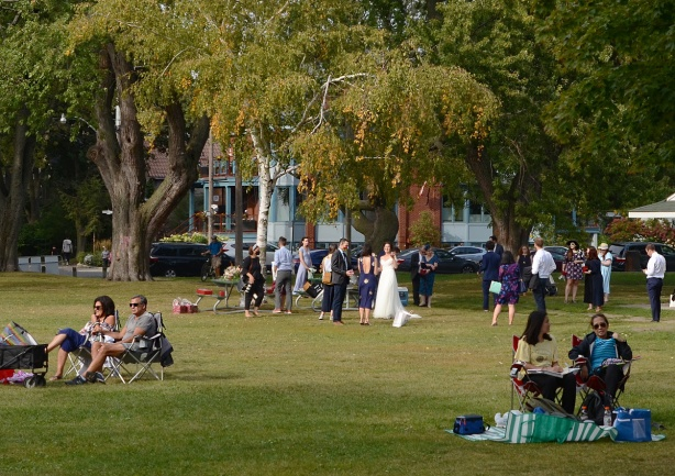 a wedding party in the park, other people sitting in the park and looking out towards Lake Ontario