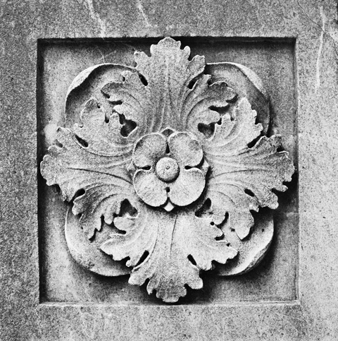 a carving in stone, square panel with a 4 petal flower with 4 leaves, symmetrical