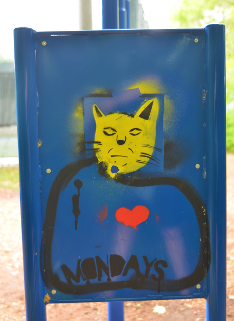 street art on the back of a blue metal sign, a yellow cat head and the words I Mondays, with a red heart between I and Monday, therefore I love Mondays