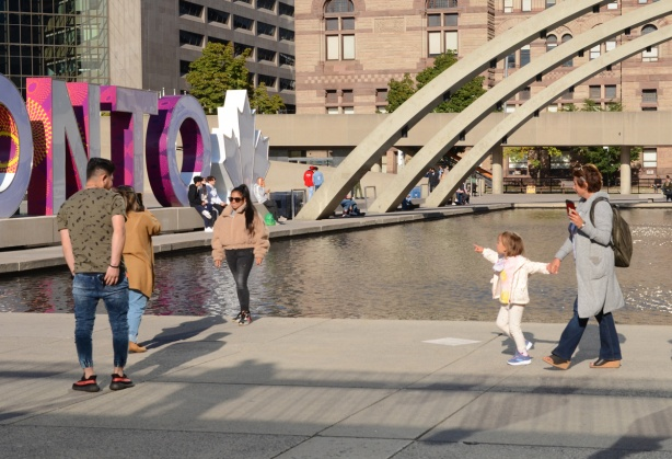 a young girl pulls her mother towards the toronto sign while she points at it, others are taking photos in front of the sign