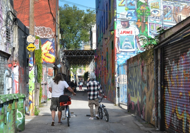 two young men walking their bikes down Graffiti Alley