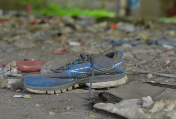 a black and blue running shoe with black laces on the ground under the Gardiner, among other pieces of garbage strewn about