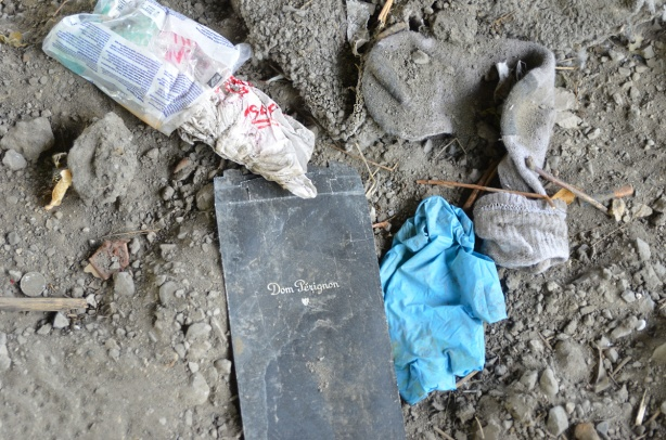 a flattened empty black Dom Perignon box, blue plastic disposable gloves, dirty torn wool socks, empty plastic bag, garbage found in the dirt and rocks under the Gardiner