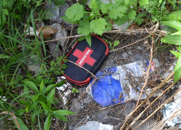 a red and black naloxone case on the ground, in the weeds, also a flattened milk carton