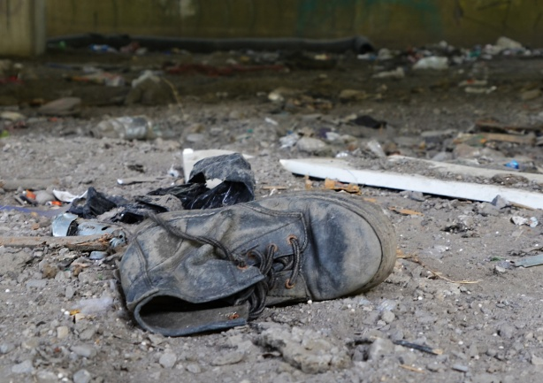 an old black boot lying on its side, laces undone, well worn, old, scuffed up, lying in the dirt, a black plastic garbage bag crumpled up is behind the shoe