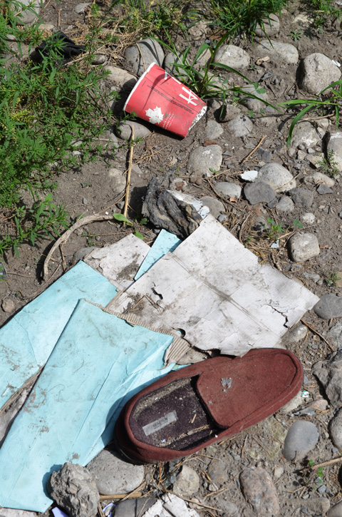 an old brown slipper, some turquoise and white paper, and an empty and squashed red Tims coffee cup, all rubbish lying on the ground