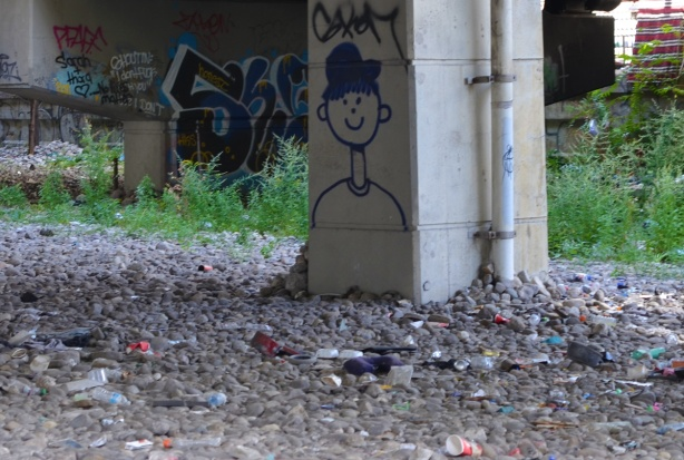 on a pillar for the Gardiner, a drawing of a man with a smiley face and a black hat, head and shoulders only. Stones cover the ground around it, lots of rubbish among the stones