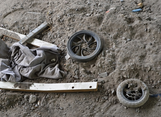 2 small wheels, not the same, and some pieces of wood, in the dirt,