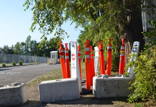 a collection of orange bollards for traffic, sitting beside the road and driveway leading to a parking lot. Parking lot booth in the background, empty