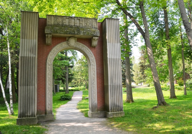 an arch entranceway of red brick and stone over a path through a garden with lots of trees and grass around it