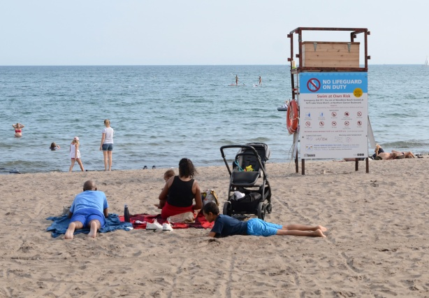 a family sits together on the beach, the youngest is a baby in mother's lap. stroller is beside them, empty lifeguard station too