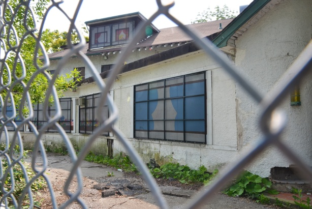 chainlink fence in front of an empty white building with windows that have been covered, old Guild Inn before renovations