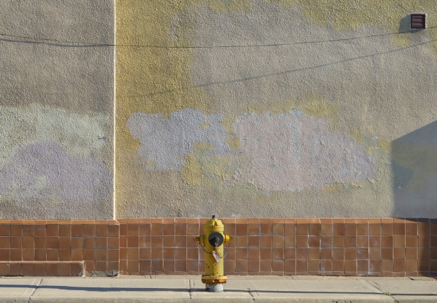 a yellow fire hydrant in front of a wall that is rust coloured tile on the bottom and grey stucco above. the stucco has been painted in splotches probably painting over graffiti